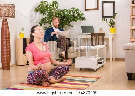 Pregnancy yoga. Fitness concept. Torso closeup of beautiful young pregnant yoga woman working out indoors. Pregnant fitness womon sitting in yogic cross legged pose at home. Prenatal meditation.