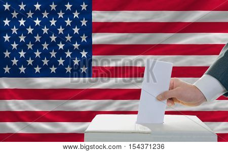 man putting ballot in a box during elections in america