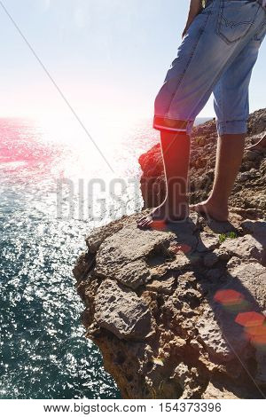 Legs of the barefoot person standing on the rock by the sea. Kontrovy light setting in the sea sun it is tinted. The man is dressed in short jeans barefoot