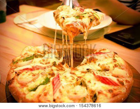 Pizza hawaiian seafood on wooden plate background - Unhealthy and Junk food. soft blur.