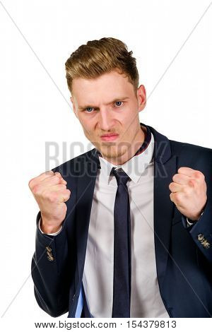 Aggressive angry young businessman raised hands and squeezed fists isolated on white