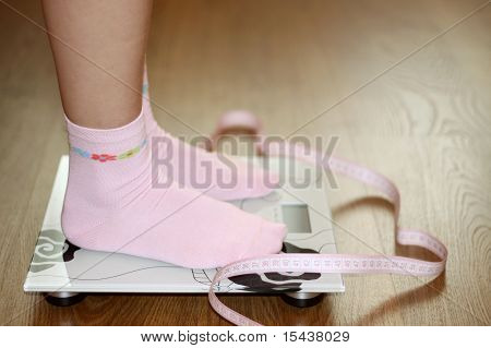 Woman on scale with pink tape measure