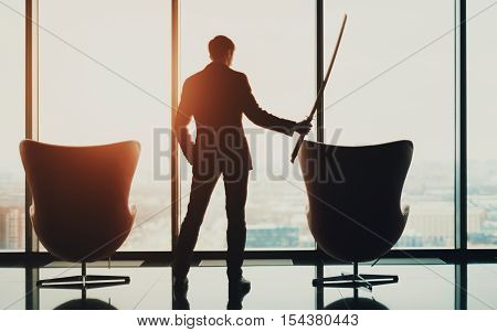 Young serious businessman in office in business suit standing between of two armchairs in front of window and holding katana sword like japanese samurai warrior blurred city top view in background