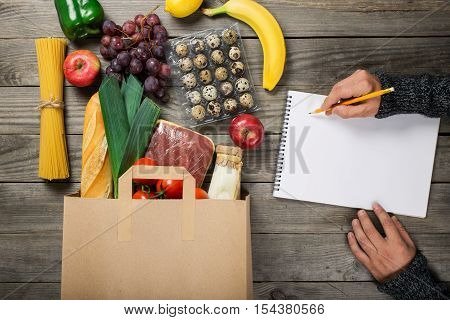 Full paper bag different food on wooden table. Man is a shopping list of food