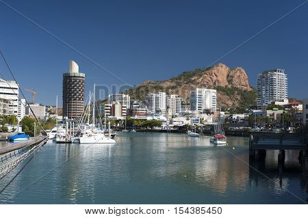 View down the quay of boats moored in the calm water of Townsville marina in Queensland Australia with modern waterfront city central architecture and a castle hill behind