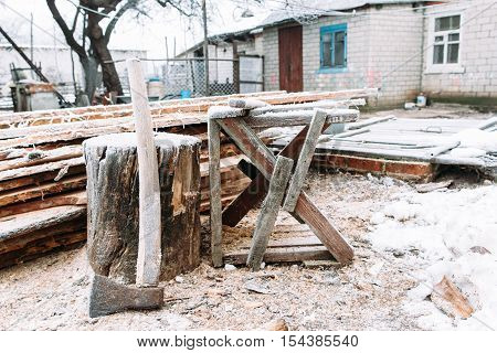 Sawhorse in winter yard. Russian winter. Place for firewood chopping, house on background. Cold, early frosts, hoar concept