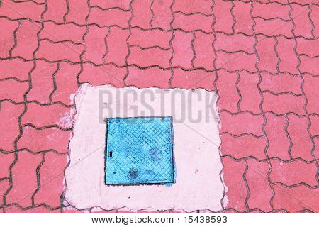 square cover on pink pavement