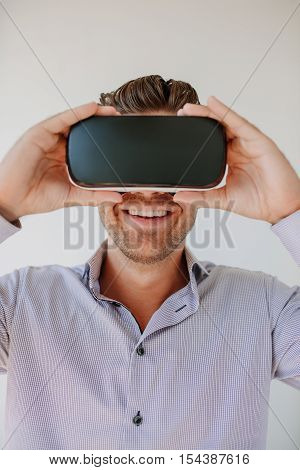Shot of happy young man wearing virtual reality goggle against grey background. Caucasian male using VR goggle and smiling.