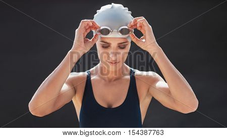 Female Swimmer In A Swimsuit Adjusting Her Goggles