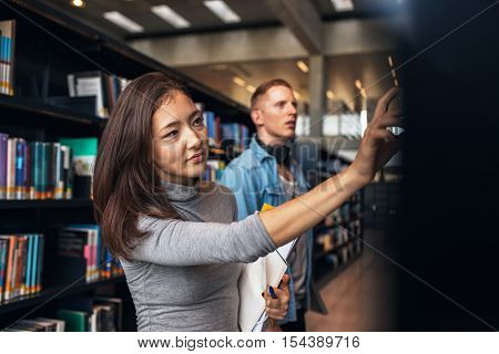 Shot of young female student selecting book from library shelf with man in background. University students taking book from shelf in library.