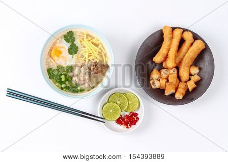 Rice porridge with mined pork and chicken lever served with side dish as Patongko (deep-fried dough stick) and spicy sour filling.