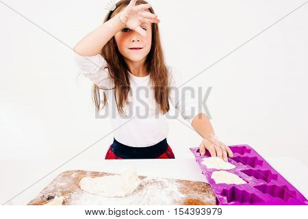 Tired girl with floured hands on kitchen. Little confectioner forming cakes, free space on white background. Homemade bakery, children culinary, pastry making concept
