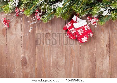 Christmas wooden background with snow fir tree and mittens decor. View with copy space