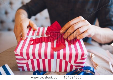 Man decorating gift box with red bow. Christmas gifts handmade wrapping. Surprise, love, friendship, surprise concept