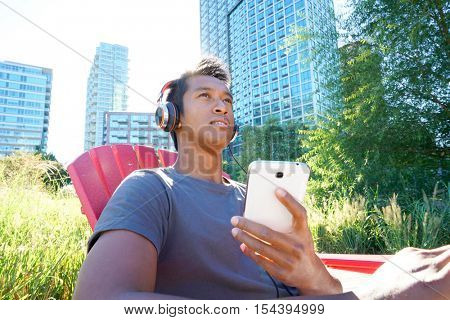 Trendy guy listening to music in park, Long Island