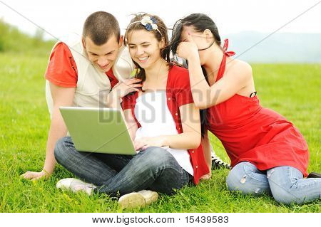 Youth on laptop together in nature