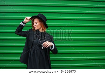 Attractive vogue model alluring outdoor by the green wall. City style. Fashion photo