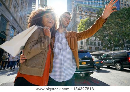 Couple in NYC on a shopping day, hailing for a taxi cab