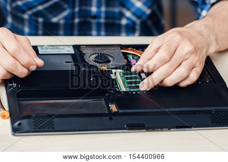 Laptop disassembling in repair shop, close-up. Engineer take microcircuit from computer. Electronic repair shop, technology renovation concept