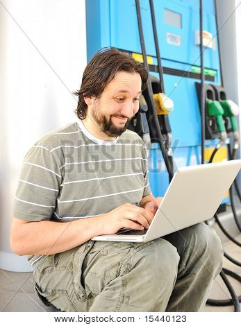 Man with laptop on gas station with silly expression on his face after reading last news