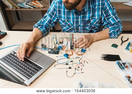 Programmer testing his new invention on laptop. Workplace of hacker, working with electronic components and computer language. Modern technologies, electronics, diy product engineering
