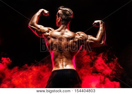 Unrecognizable man with strong muscles posing with arms up in smoke.