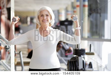 Fitness as lifestyle. Joyful sporty senior woman keeping fit and smiling while using weights during gym exercise.