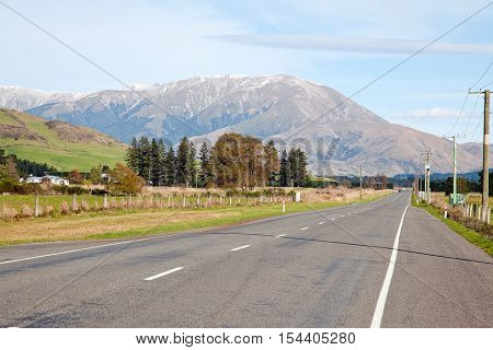 Long road stretching out into the distance with snow mountain background in New Zealand