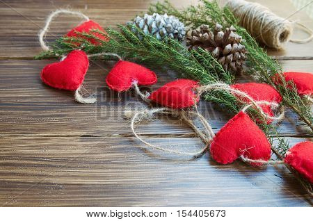 Christmas or New Year background. Natural fir tree brunch and cones with felt heart garland on wooden rustic table. Winter holidays concept. Copy space.