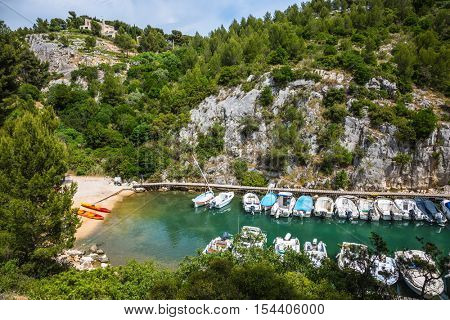 Good weather in May. Calanque National Park - small fjords between Marseille and Cassis. White sailboats moored in rows near woody shore