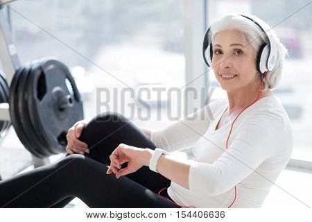 Pleasant workout. Beautiful senior woman smiling and using headphones while exercising in a gym.