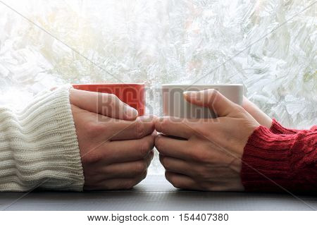 warming meeting couple in love pair on a background of frozen window with a winter pattern / share warmest feelings