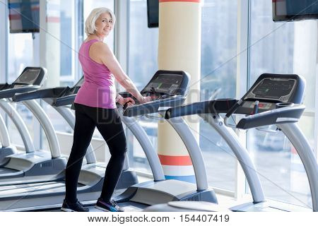 Filing healthy. Happy overjoyed senior woman smiling and doing exercises on treadmill while having workout in a gym.