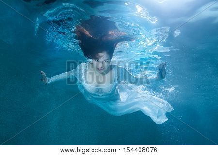 Fairy woman under the water she is wearing a white dress.