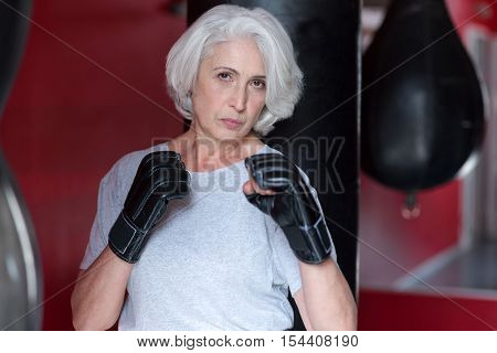 Ill be back. Senior pretty severe woman looking at you and holding hands like boxer while training in a gym.