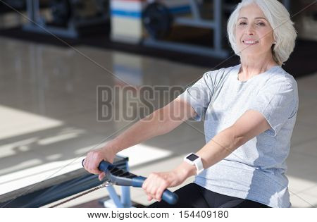 Favorite equipment. Delighted emotional senior woman laughing and using rowing machine while exercising in a gym.