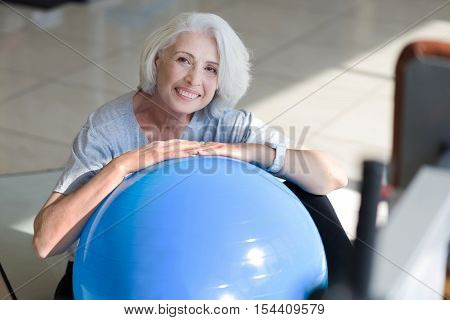 Time to relax. Overjoyed pretty senior woman sitting on a floor and putting hands on fit ball while resting after physical training