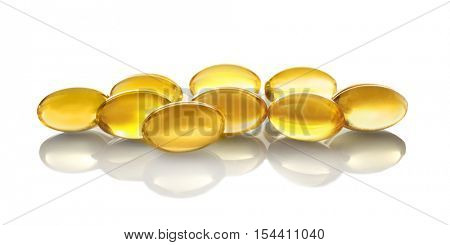 Capsules of fish oil on light background, close up view