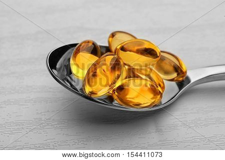 Spoon with cod liver oil capsules on white wooden background, closeup