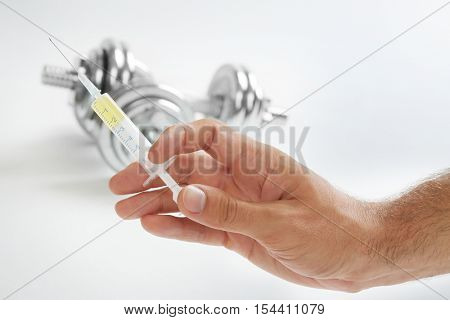 Male hand holding syringe and dumbbells in background