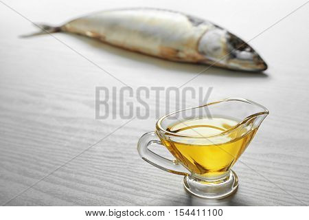 Fish oil and fresh fish on light background