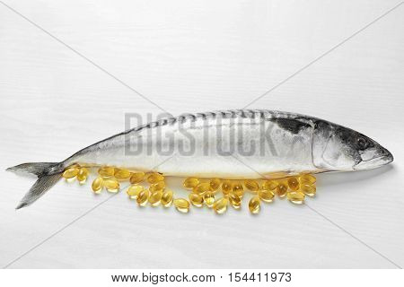Fish oil pills and fresh fish on light background