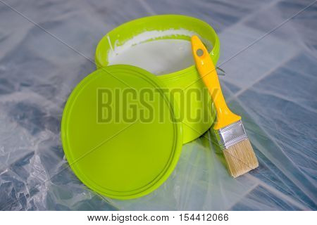 Yellow paint brush and green bucket on the floor ready for housework project and walls redecoration