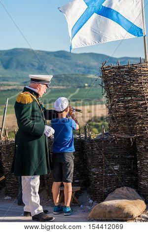 SEVASTOPOL, RUSSIA - SEPTEMBER 11, 2016: A border war is looking through binoculars. Crimean War on Crimean Military Historical Festival