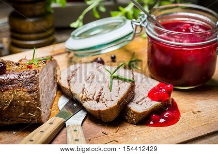 Closeup of venison with cranberry sauce on old wooden table