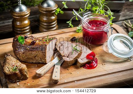 Healthy venison with cranberries and rosemary on old wooden table