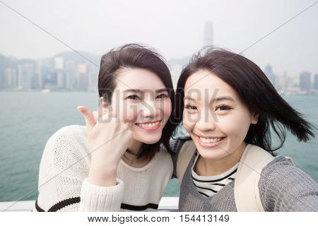 two beauty woman thumb up and selfie in hongkong