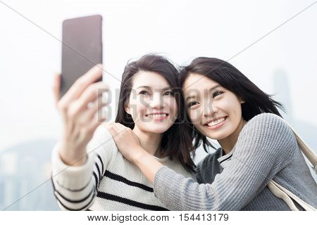two beauty woman smile happily and selfie in hongkong