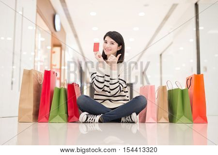 happy shopping young woman show credit cardsit on the floor in the honkong asian