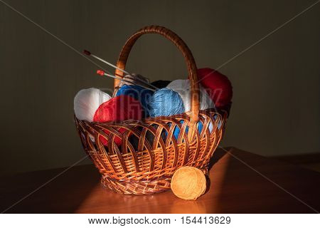 multicolored tangles lie to a basket with knitting needles and products